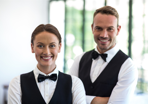waiter and waitress in smart uniform smiling at camera