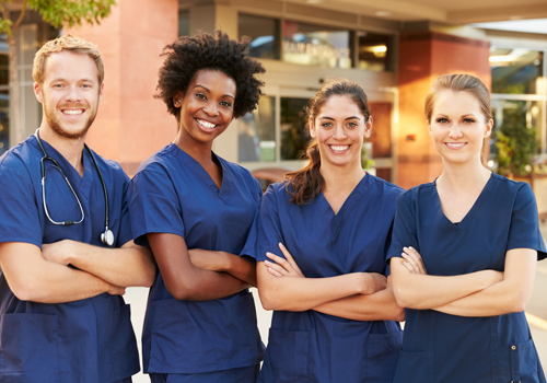 Group of female doctors in hospital scrubs smiling