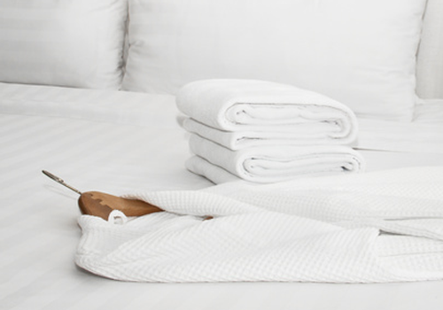 Hotel bathrobe and towels laid on bed